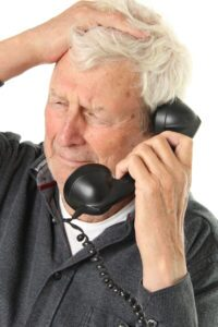 Older man on phone with scam artist