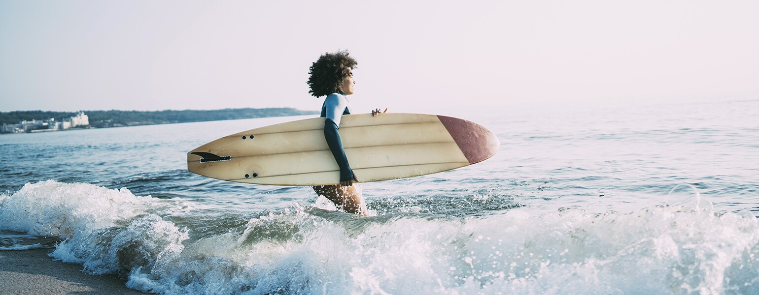 photo_of_african_american_woman_walking_in_ocean_with_surfboard_Surfing_GettyImages-1013089202_1540