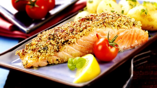 A close-up view of baked salmon with a pesto crust on a plate
