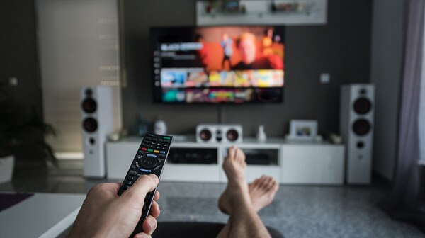 The hand of a person using a remote control on a TV in the background