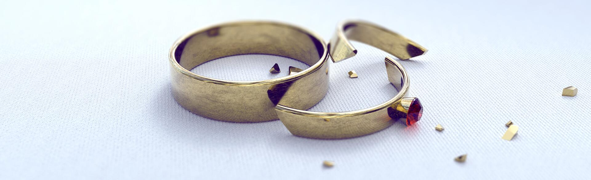 wedding band and cracked engagement ring on a white background