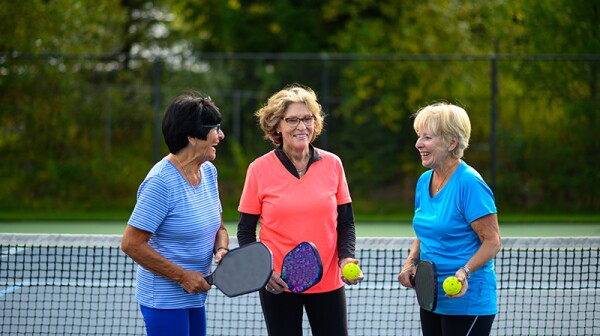 Three women standing together on a pickleball court