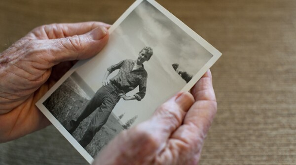 A close up of older hands holding an old photo of a young man