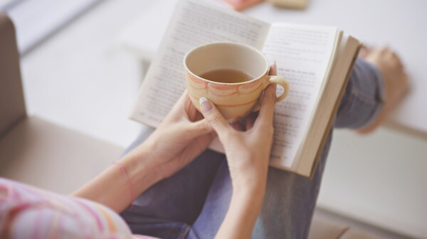 woman reading holding a teacup