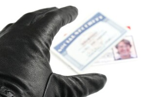 Hand with black glove reaching for Social Security card and driver's license