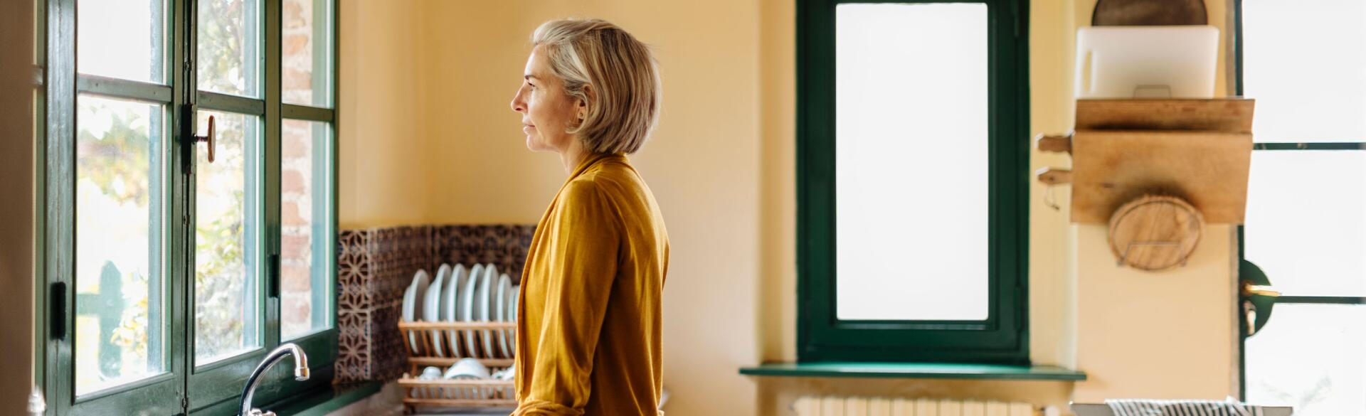 Woman standing in a kitchen at the sink looking out a window