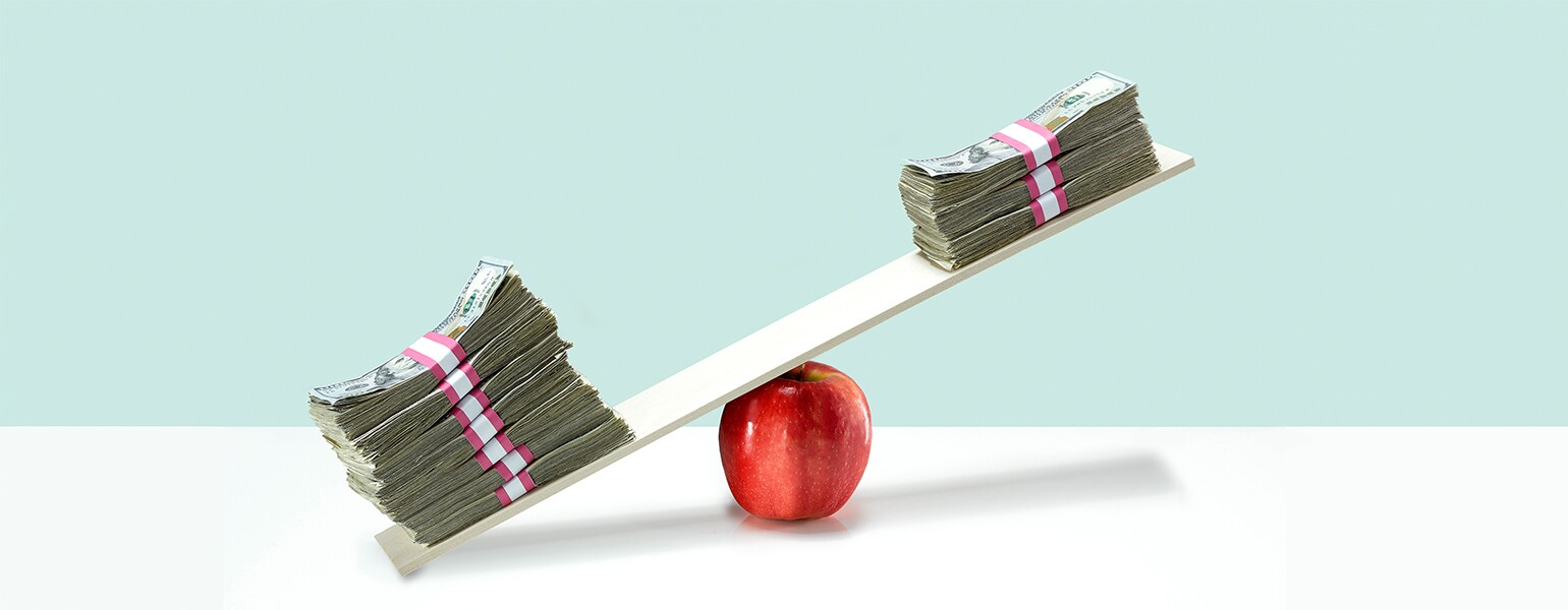 image of money on balance scale on top of apple