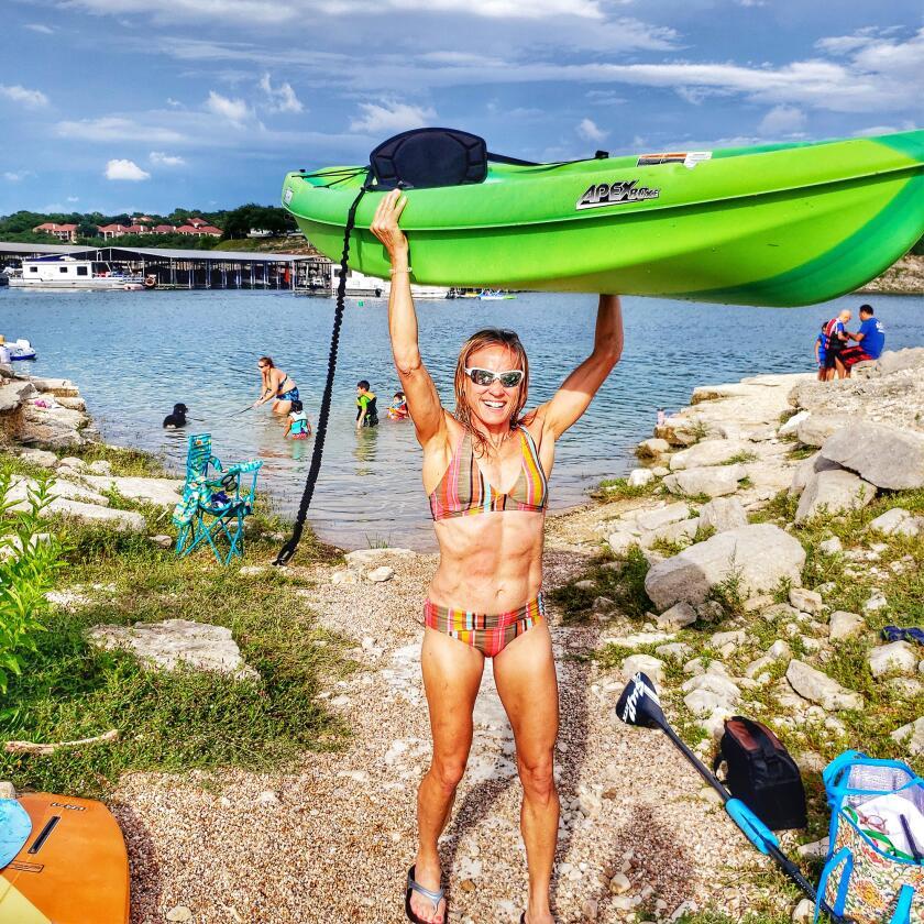 Jennifer Fisher holds a kayak above her head.
