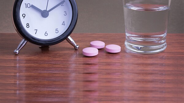 An up-close view of an alarm clock, pills and glass of water