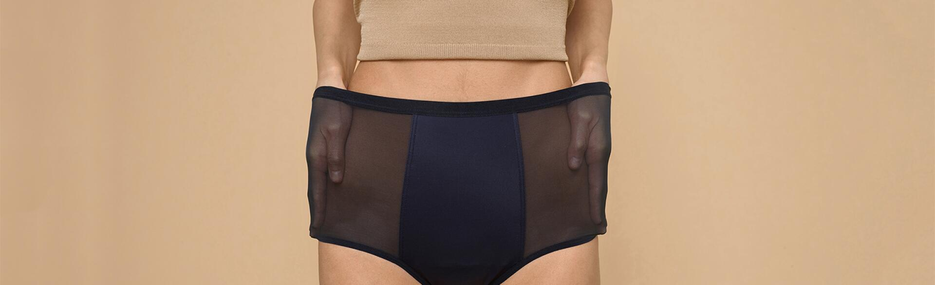 A woman stretches out the sides of her Thinx hi-waist panties, which can double for bladder leakage.