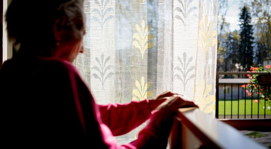Disabled senior woman in wheelchair at home in living room