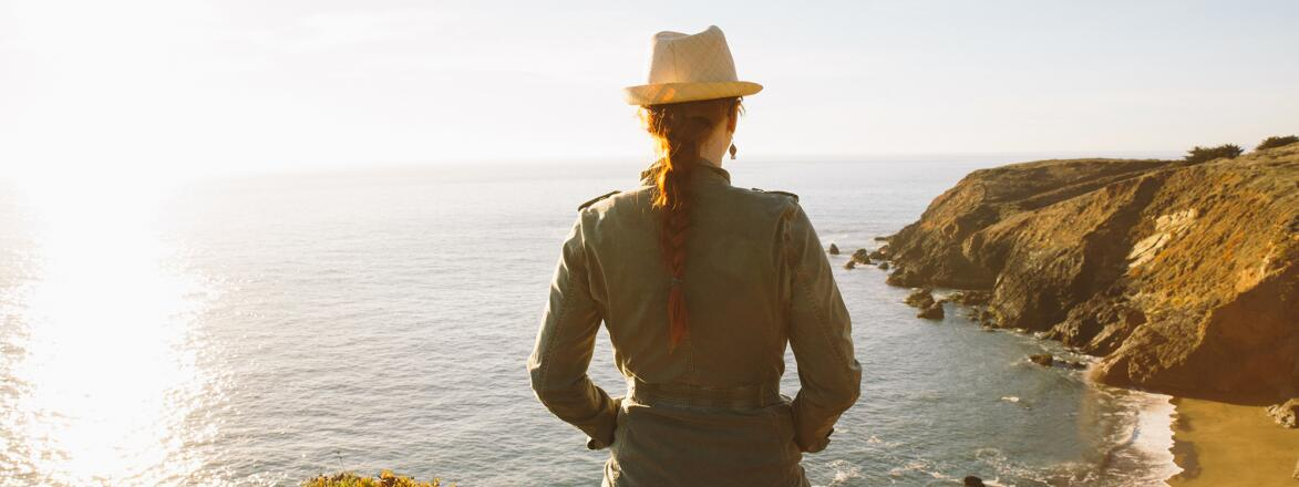 Woman in nature looking at view of pacific ocean