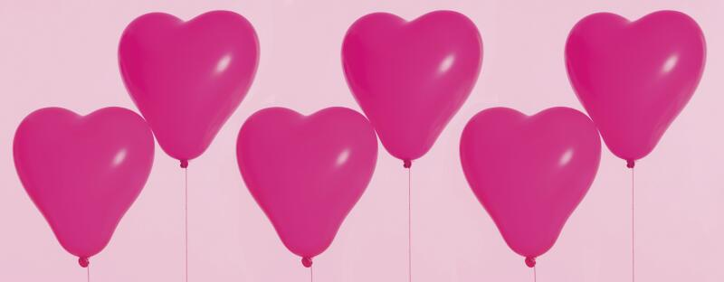 six pink heart balloons floating