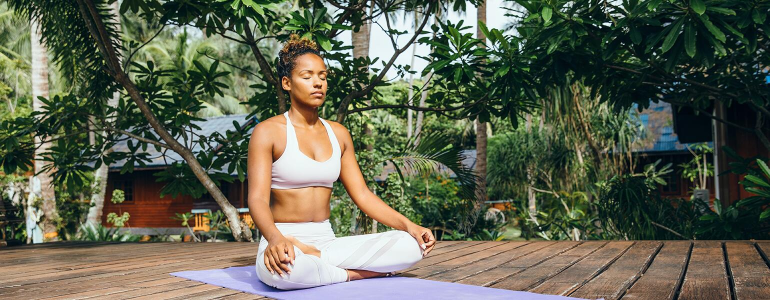 A photo of a woman sitting cross-legged on a yoga mat as she practices mindfulness and meditation.