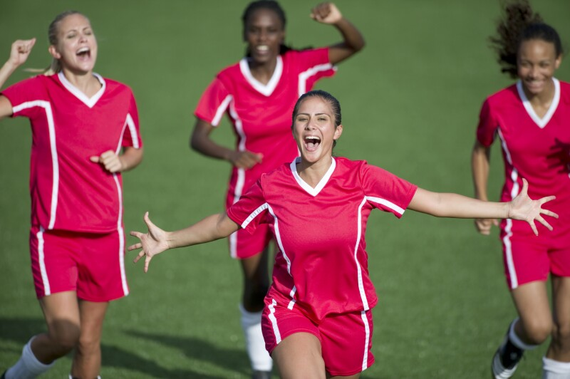 Female soccer players celebrate a goal