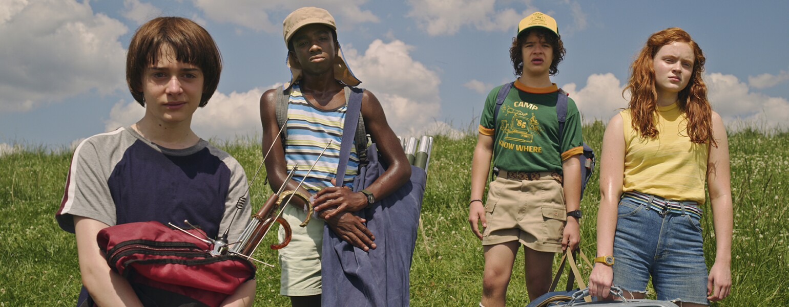 Awesome TV shows Stranger Things cast in a field from season 3