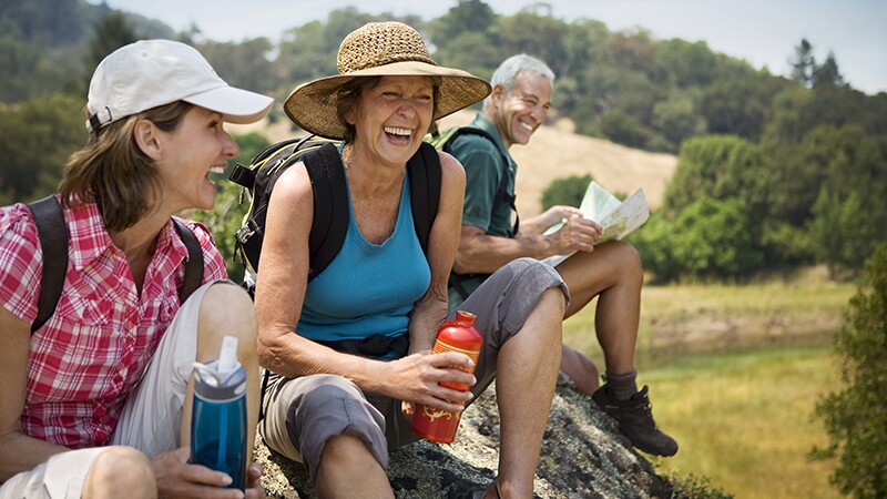 Hikers sitting on a rock and laughing