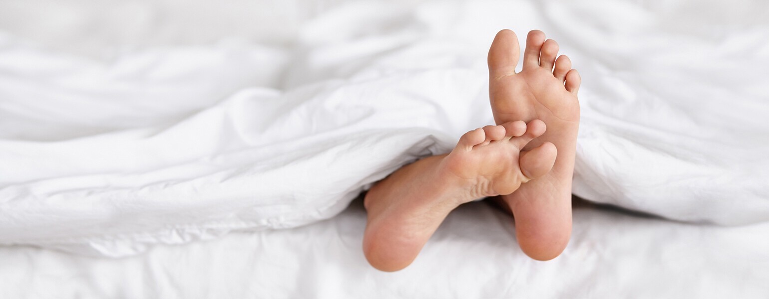 An image depicting two feet sticking out from underneath a white blanket in bed.