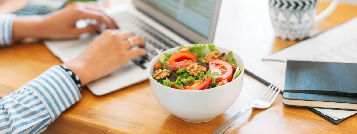 Woman typing on laptop eating a salad