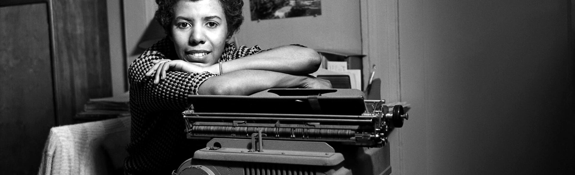 Black and white photo of Lorraine Hansberry leaning on a typewriter.