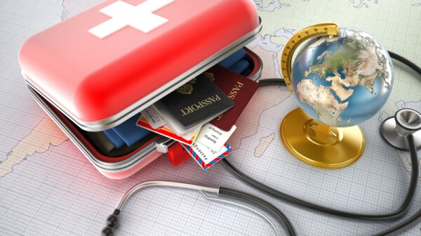 First-aid kit designed as a suitcase with passports, plane tickets and clothes inside, stethoscope and globe standing on world map. Medical tourism concept.