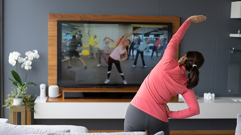Back view of a woman stretching as she watches an exercise class on TV