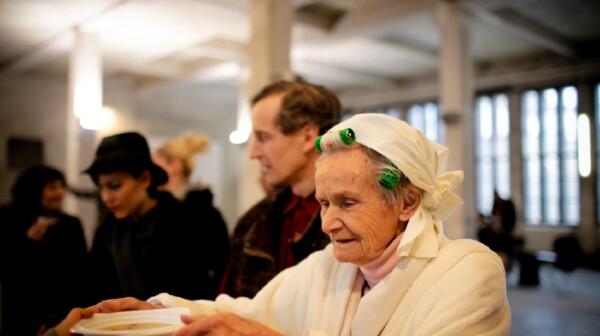 Woman eats soup at soup kitchen