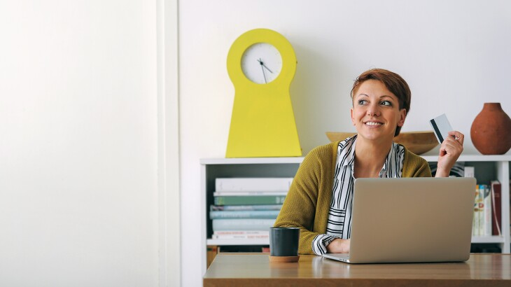 Woman at home with laptop and credit card at desk