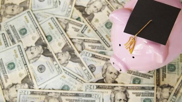 piggy with graduation cap on money