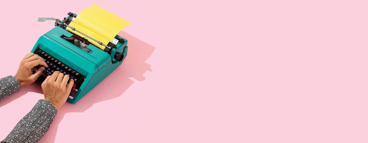 Woman writing on a teal typewriter on a pink background