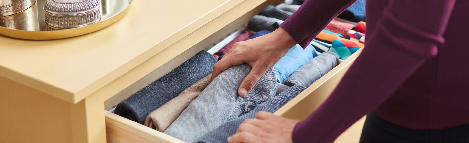 Woman organizing clothes in a dresser drawer