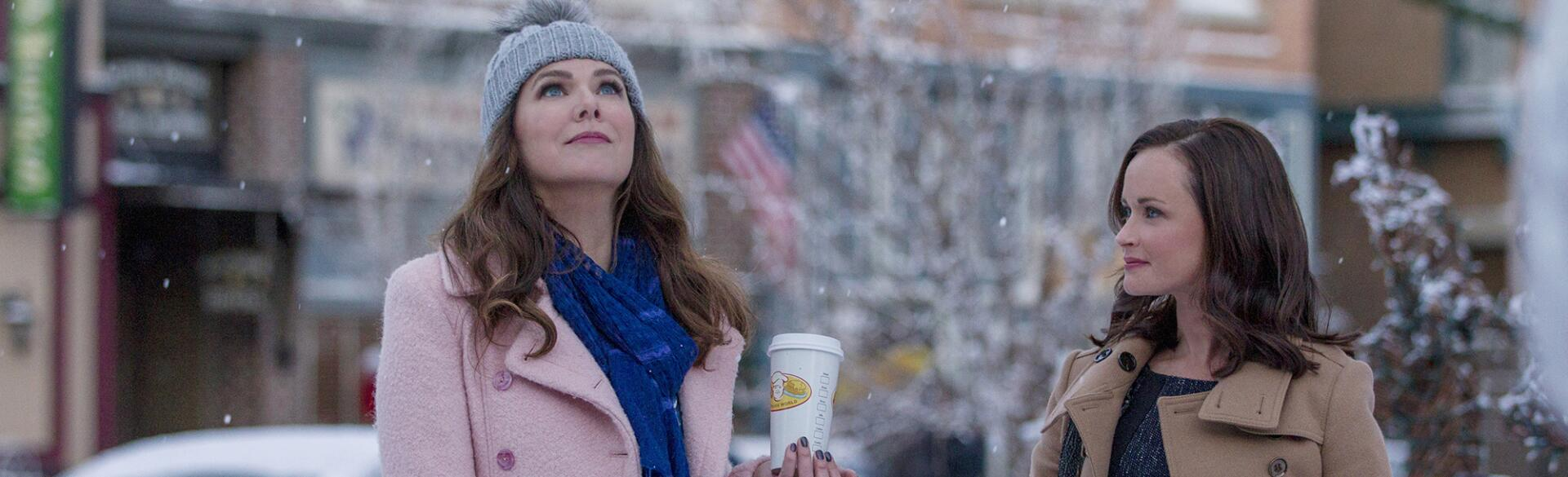 main characters from Gilmore Girls, Lorelai and Rory, outside in the snow holding coffee by a newsstand