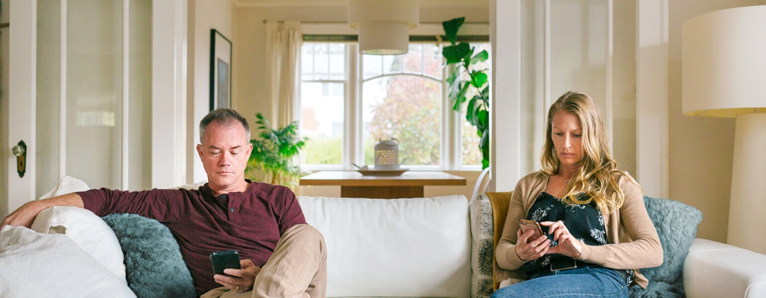 An image of a husband and wife sitting on opposite ends of the couch, distracted from each other by their cellphones.