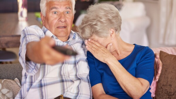 Senior couple watching a horror movie on television