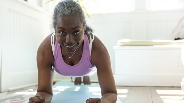 A smiling woman doing a plank on a yoga mat
