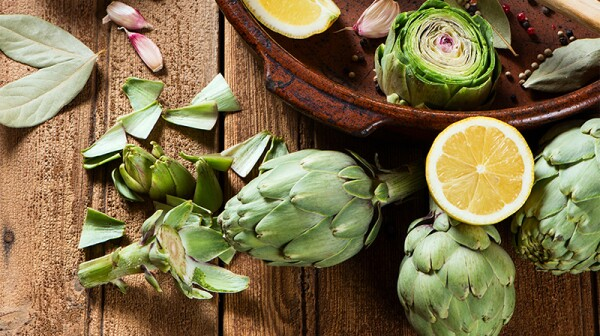 A close-up view of raw artichokes with olive oil and spices on a wooden background