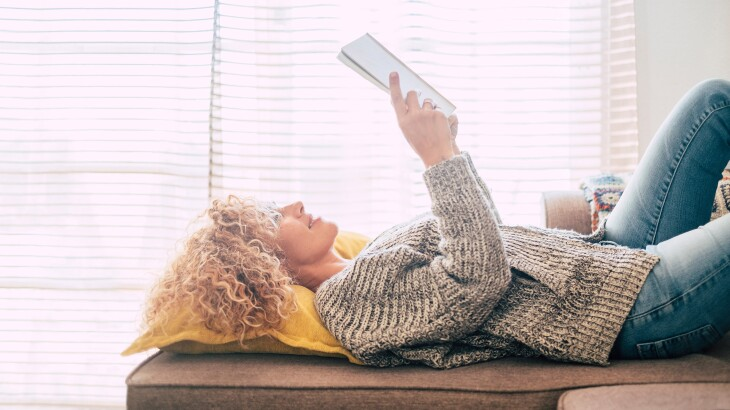 woman reading a book while lying down on a couch