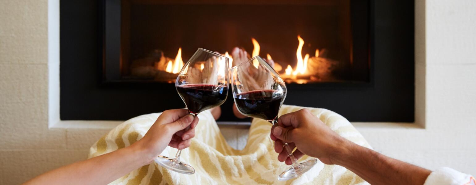 Couple with two glasses of red wine in front of a fireplace.