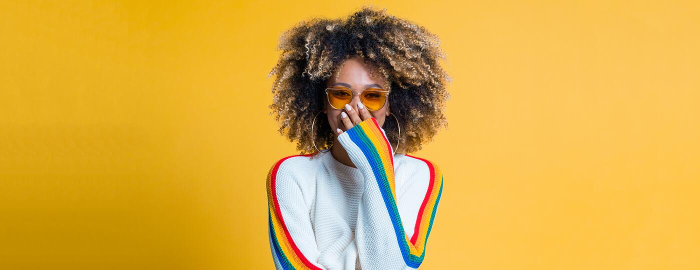 Surprised afro girl standing against yellow background showing her beautiful curls
