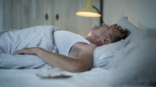 A man appearing stressed as he sleeps in bed
