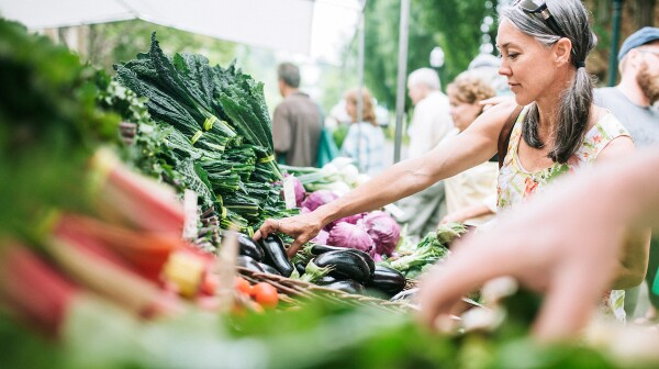 silver-haired woman shopping vegetables at farmers market