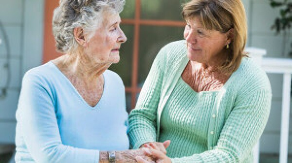 Caregiver helping senior woman on a walk