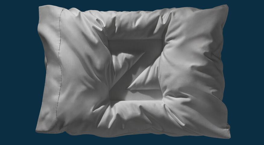 a fluffy pillow with the letter Z pushed into it, on a navy blue background