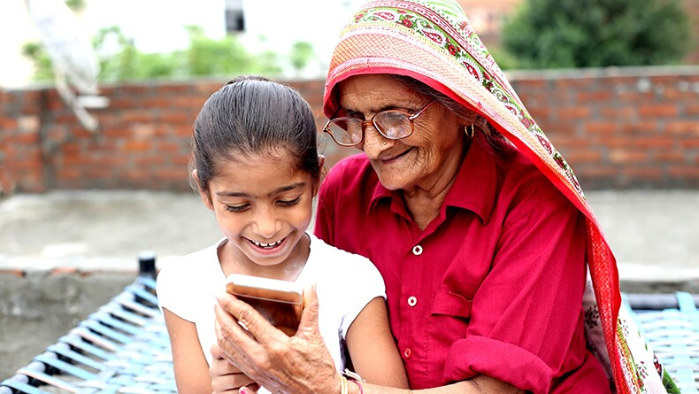 Grandmother and granddaughter look at a smartphone