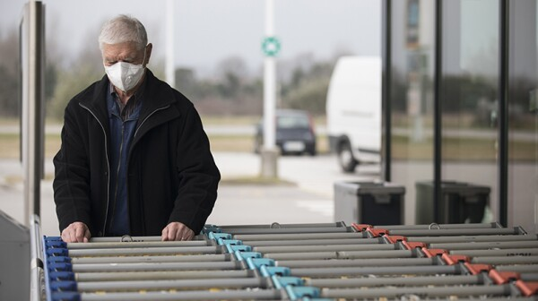 An older man wearing a protective face mask chooses a shopping cart at the supermarket