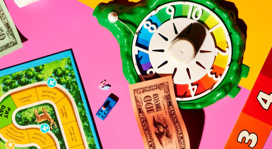 a game night involving paper money, and a number spinner, bright rainbow colors
