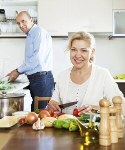 happy ordinary mature couple cooking food with vegetables