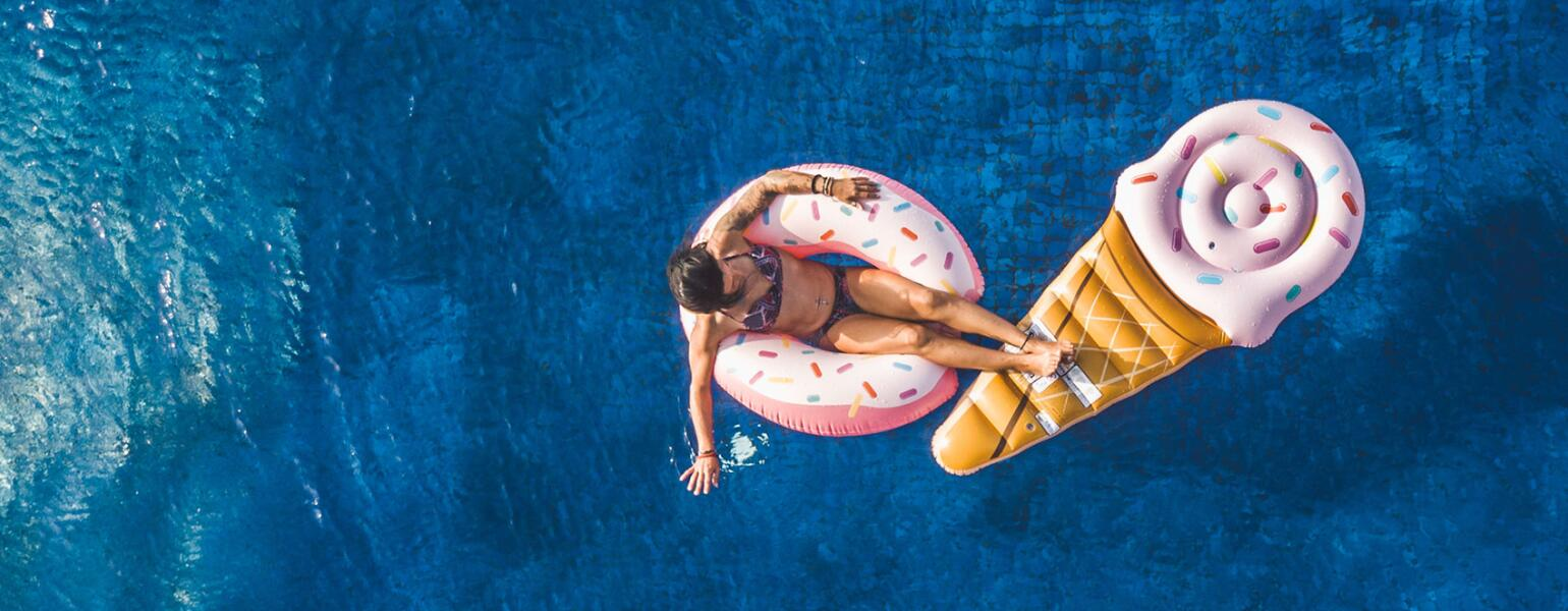 Young Woman Floating In Big Swimming Pool On Inflatable Donut