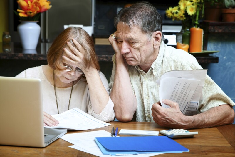Senior couple at home with many bills