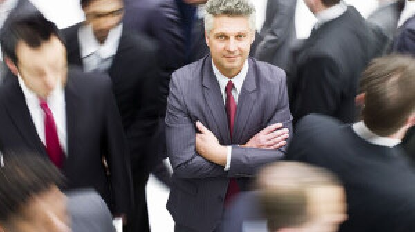 Older Job seeker standing out in crowd